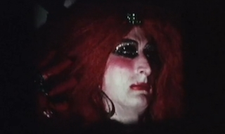 Man in drag and red wig