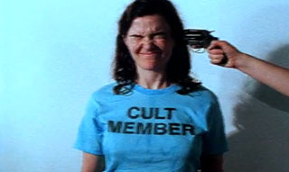 Cult member has a gun pointed at her head