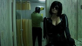 Melodie Sisk as a dominatrix making her client clean a motel bathroom