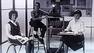Three students sitting around a school movie projector
