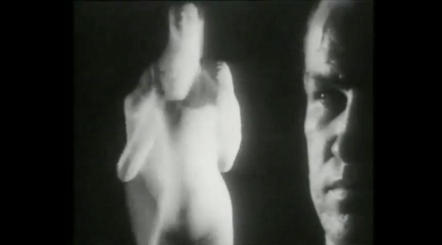 Close-up of a man's face looking at a blurry dancer