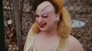 Film still from Pink Flamingos featuring Divine eating dog poop