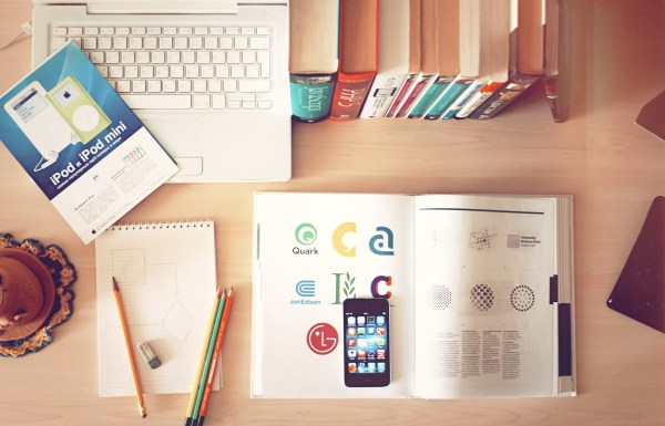 The top view of creative designer's office showing books, pencils, laptop, and iphone on a desk