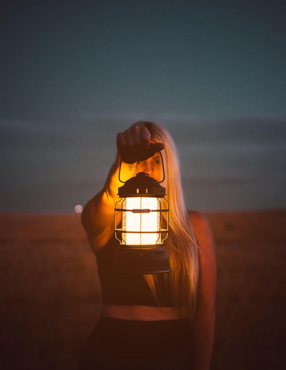 medium resolution of shallow focus photography of woman holding lantern