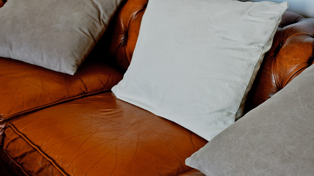 white pillow on brown leather couch