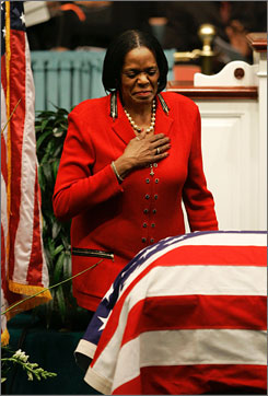 Rep. Carolyn Kilpatrick, D-Mich., pauses at the flag-covered casket of Rep. Julia Carson after delivering remarks during funeral services in Indianapolis, Saturday.