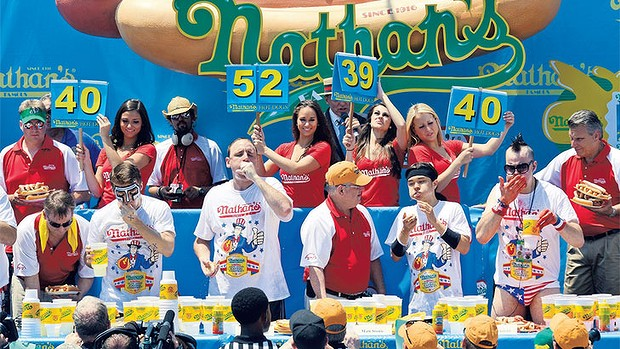 Conspicuous consumption: Joey Chestnut (second competitor from left) wins Nathan's famous Fourth of July International Hot Dog Eating Contest in Coney Island in July.