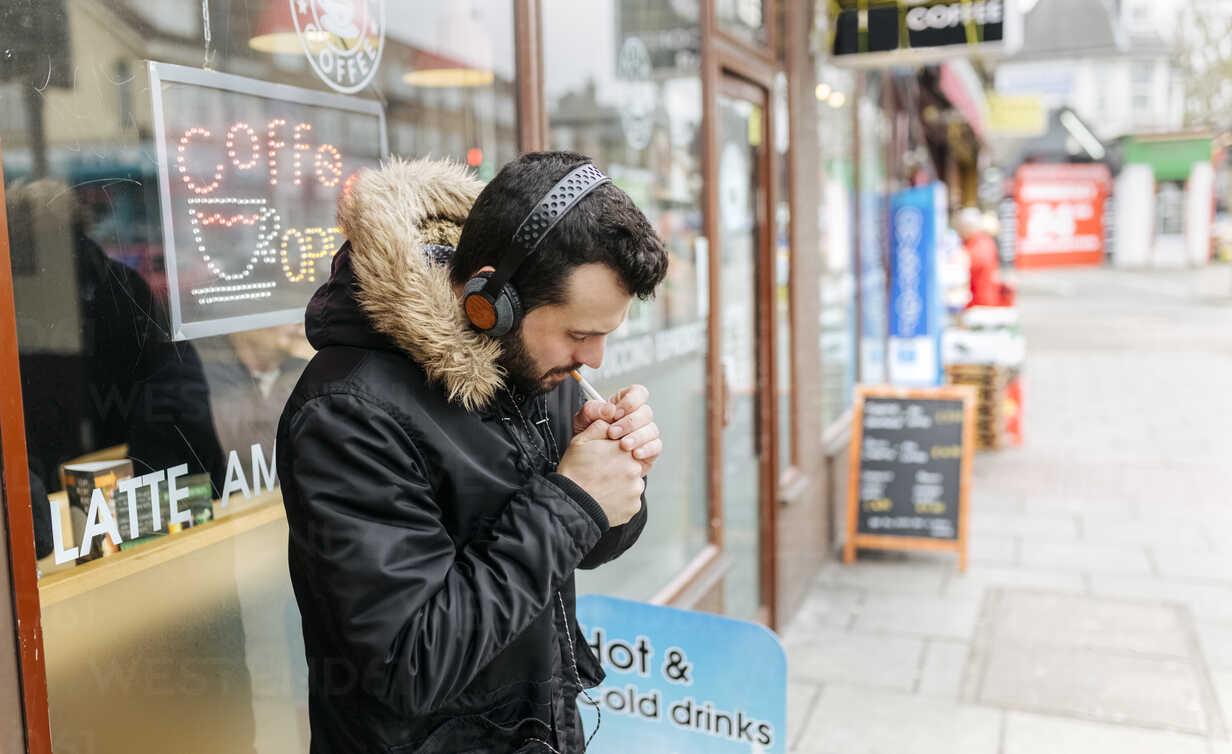 https www westend61 de en imageview mgof001685 uk london man with headphones standing in front of window display lighting a cigarette