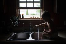 playful boy washing legs while sitting