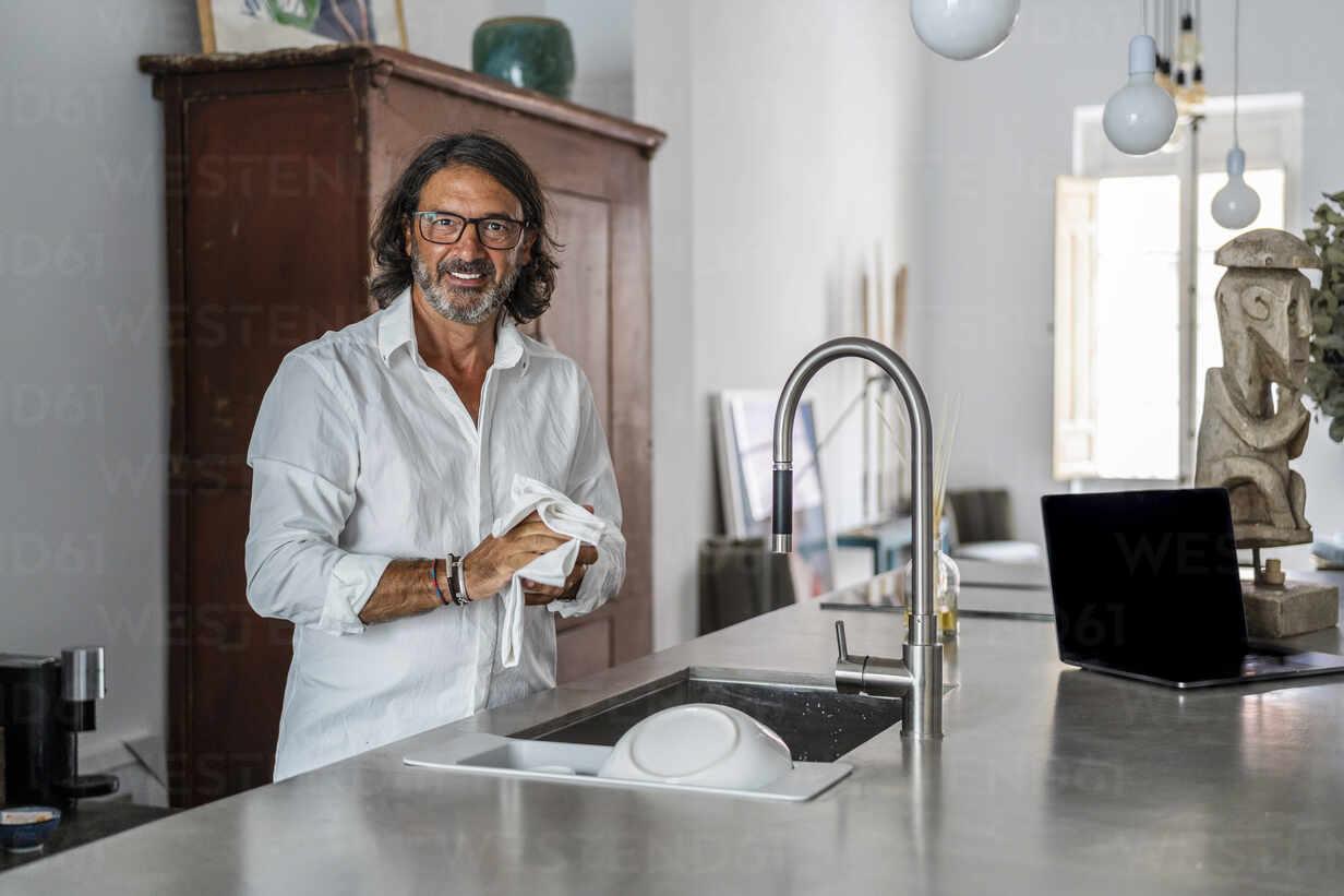 https www westend61 de en imageview dltsf01147 smiling man cleaning crockery while standing by sink in kitchen