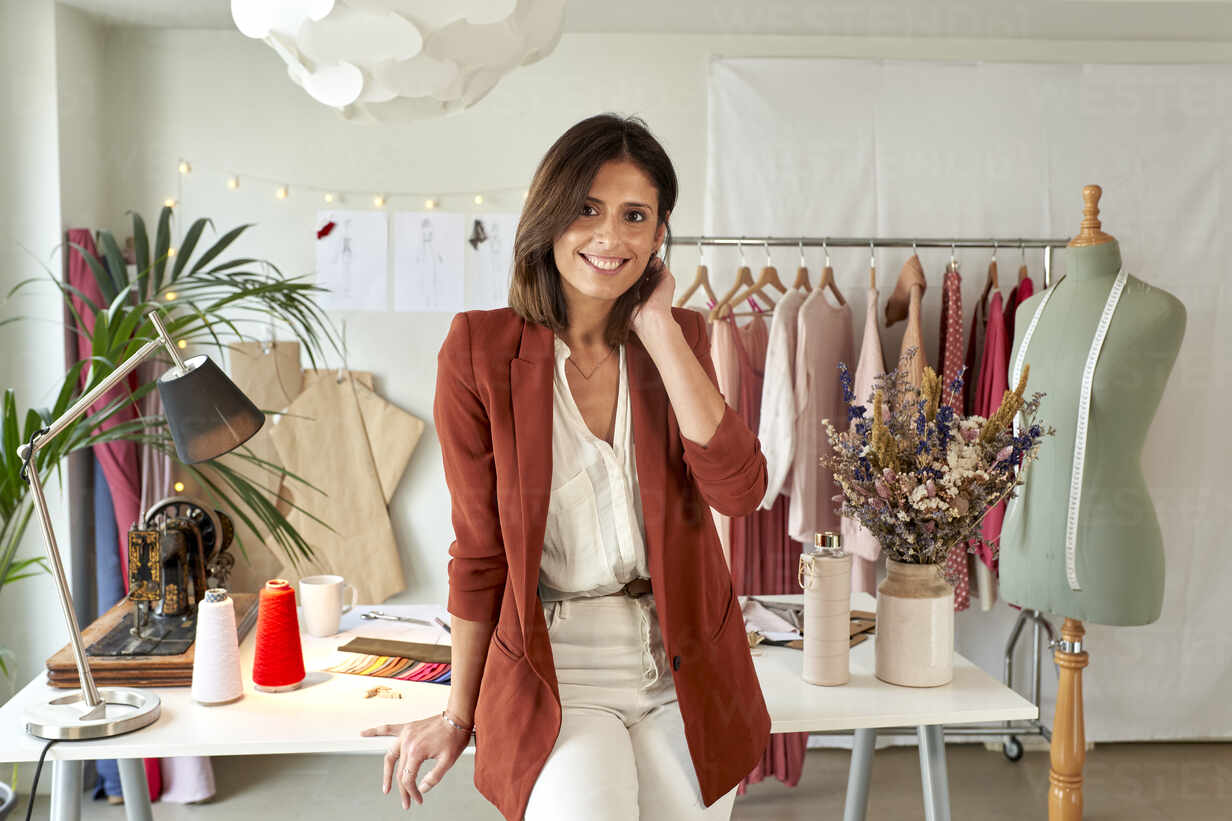 confident female fashion designer leaning on desk against clothes rack at atelier stockfoto