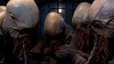 Image of the tentacle-faced Ood huddled in a circle, looking hopeless and dejected.