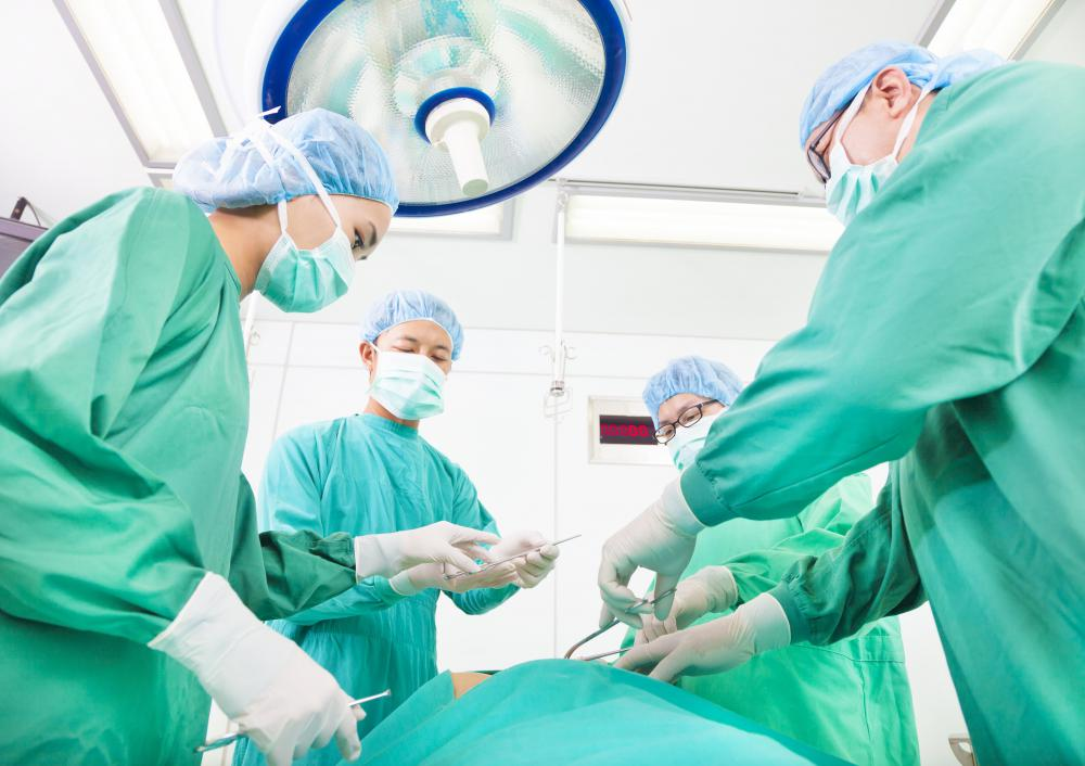 https://i0.wp.com/images.wisegeek.com/four-surgeons-in-green-gowns-and-masks-standing-over-patient.jpg