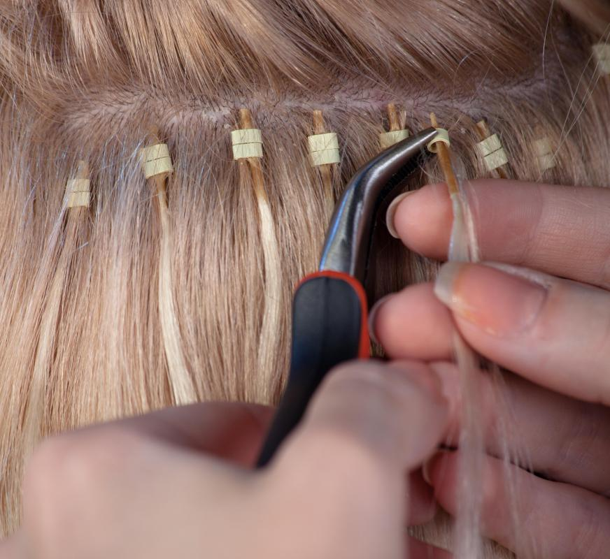 A Stylist Putting In Hair Extensions