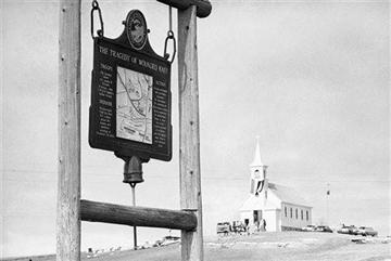 (AP Photo/File). FILE - This undated file photo shows the historical marker commemorating the Wounded Knee Massacre of 1890 on the road near the Sacred Heart Catholic Church in Wounded Knee, S.D.