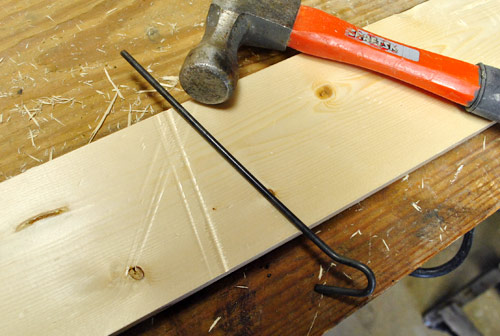 using metal rod and hammer to create long dents in new wood board to make it look old and beat up