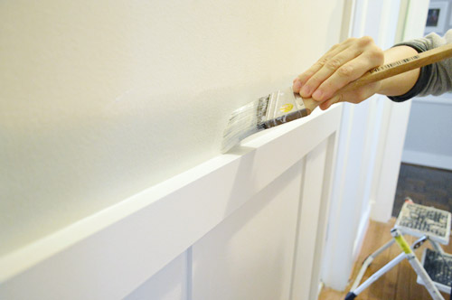 edging with a paintbrush to apply gray paint above a chair rail in hallway