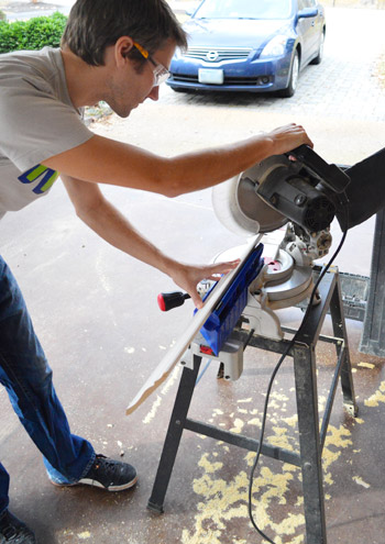 John using miter saw to make cut on crown molding