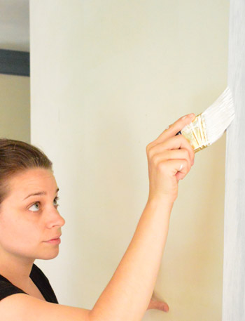 Sherry painting trim white with short handled paint brush