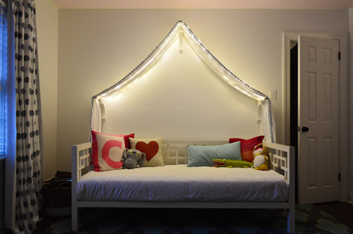 adding fairy lights to a canopy bed