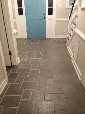 side by side comparison of clean bright grout and dirty discolored grout from using grout paint in foyer