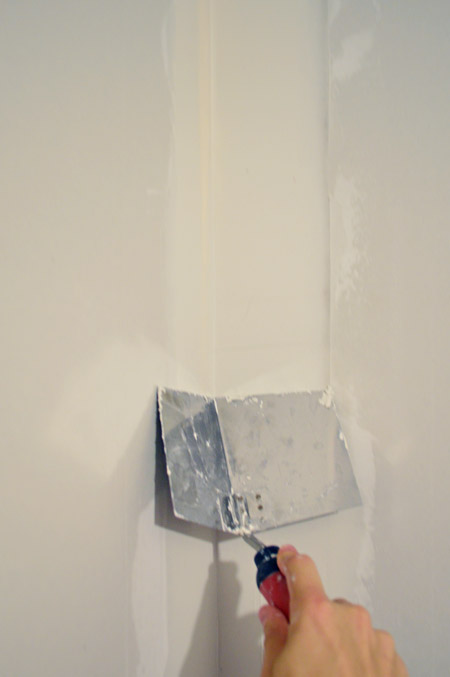 dragging corner trowel down corner of drywalled wall