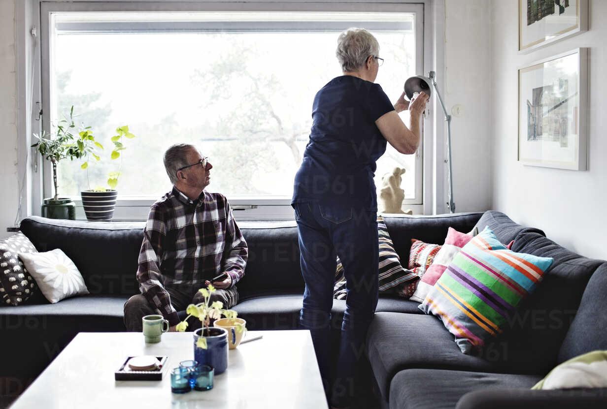 https www westend61 de en imageview masf07415 senior man looking at woman adjusting floor lamp by sofa in living room