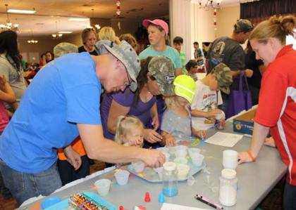 Family members visit the sand art table to make colorful creations during the Month of the Military Child event at Thunder Mountain Activity Centre, Fort Huachuca.