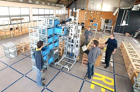 """גיא גלס (באפור, עם הפנים אלינו) ועובדי Caja מתרגלים אבטיפוס של הרובוט """"אלונה"""". הוא מסוגל גם לשלוף את הארגזים, וגם לבנות מחדש את המדפים בסידור ובגובה שיתאימו לצרכיו"""