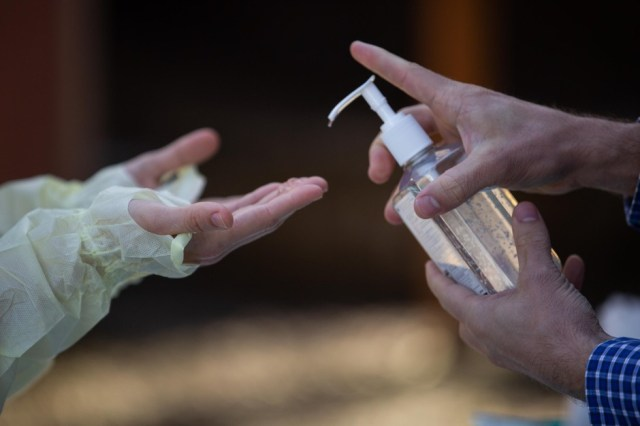 Oregon Health & Science University nurse practitioner Shelby Freed (left) sanitizes her hands between glove changes on Friday, March 20, 2020, in Portland, Ore. Testing for COVID-19 requires regular changing out of PPE like gloves, masks and gowns, but a nationwide shortage has prevented many health care workers from doing so.