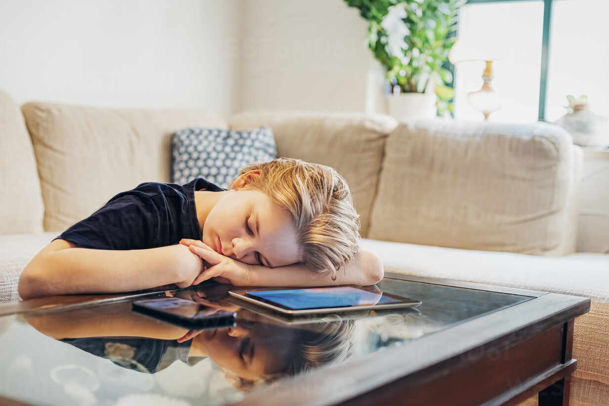 https www westend61 de en imageview mjf02458 boy lying on coffee table with smartphone and tablet taking a nap