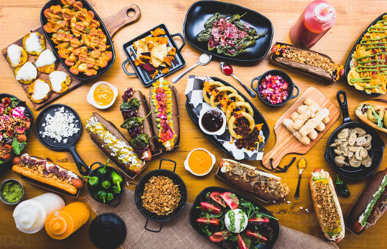 https www westend61 de en imageview adsf02530 flat lay of table served with great amount of various snacks and hot dogs with sauces and spices