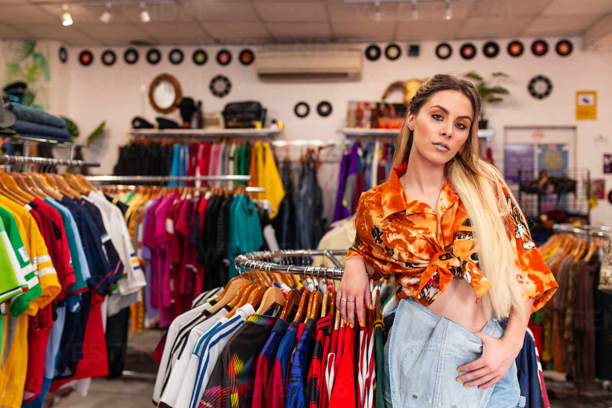 attractive young female in trendy outfit leaning on clothes rack and looking at camera while standing