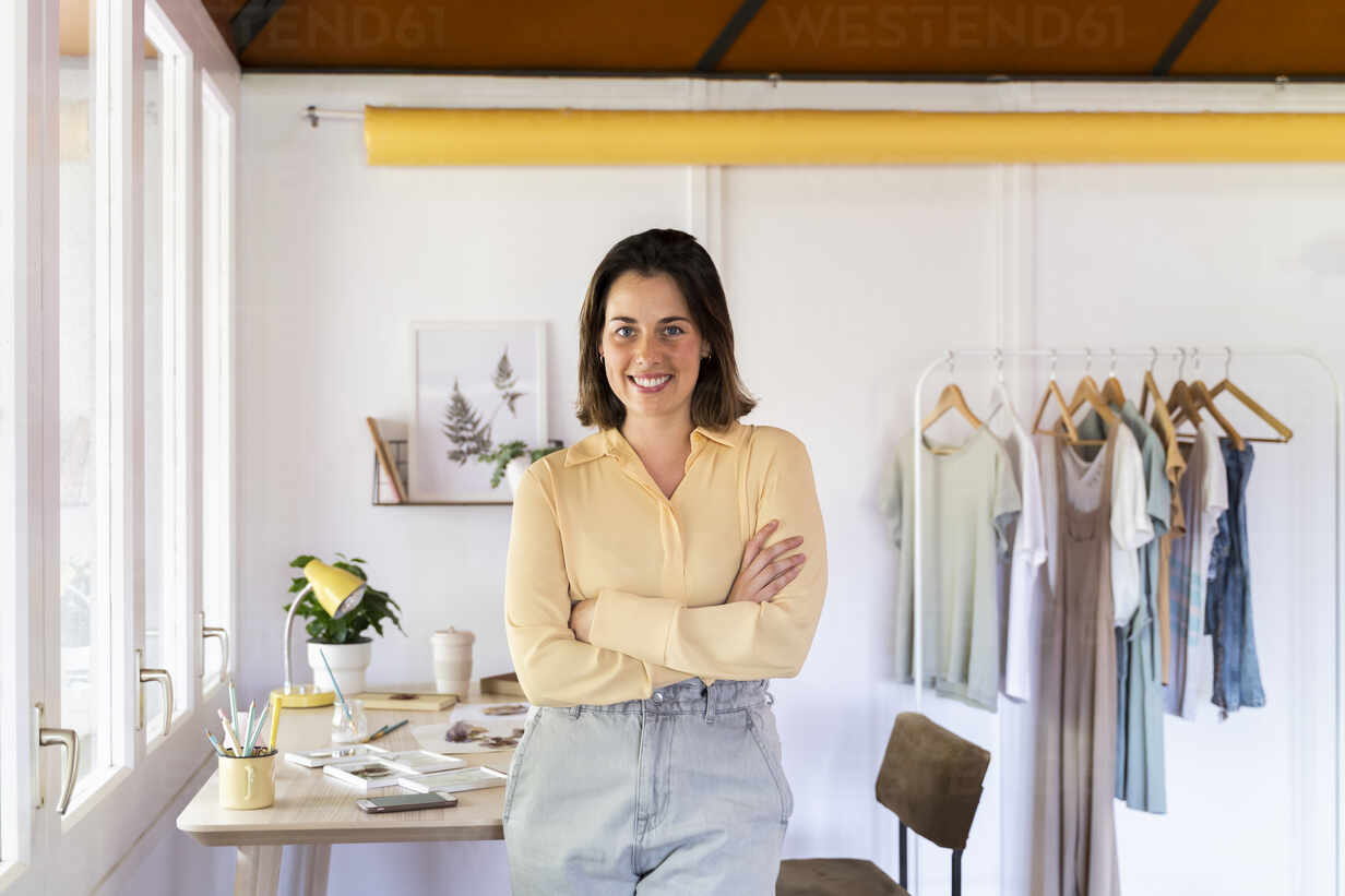 https www westend61 de en imageview afvf07024 smiling young female fashion designer with arms crossed leaning on table at clothing store