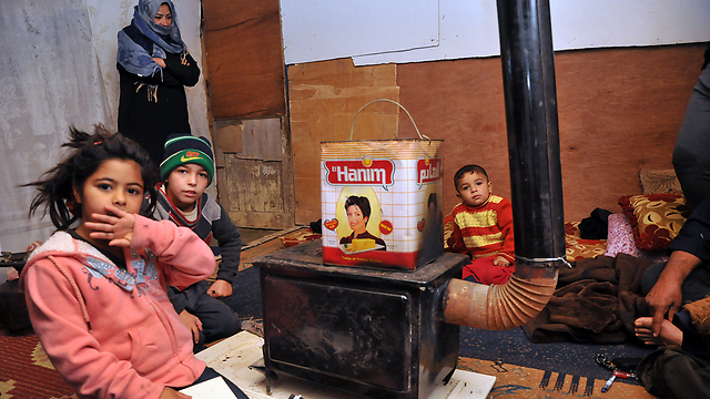 Children huddle around heater in refugee camp (Photo:AFP)