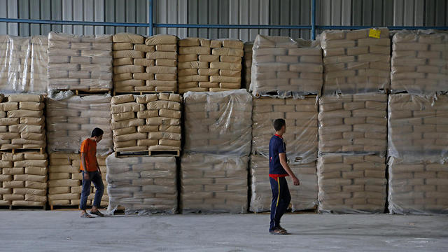 Palestinian workers check bags of cement at a warehouse (Photo: AP)