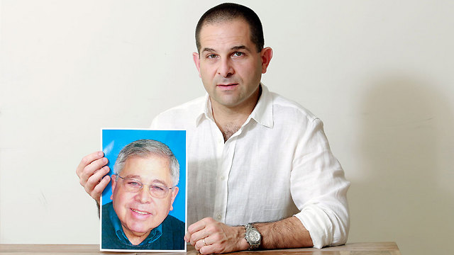 """מיכה אבני עם תמונת אביו, ריצ'רד לייקין ז""""ל (צילום: דנה קופל)"""