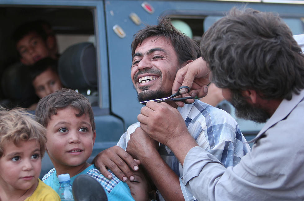 Men cut their beards in Manbij after the city's liberation by SDF forces. ISIS imposes a strict Islamic dress code on the population under its control