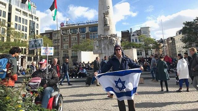 Un Juif à Amsterdam manifestant seul devant un drapeau israélien devant le BDS (