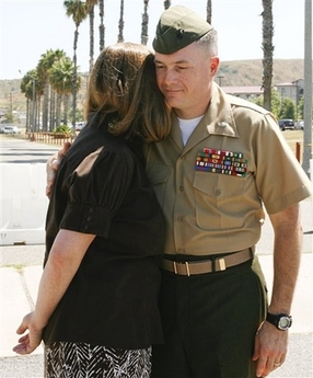 Marine Corps Lt. Col. Jeffrey Chessani, right, hugs his wife Alissa Chessani, after charges against him were dismissed
