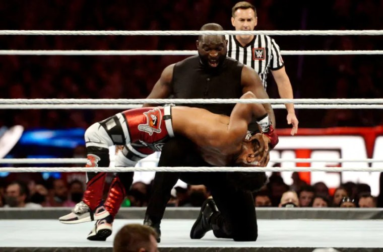 Apr 10, 2021; Tampa, Florida, USA; AJ Styles (silver pants) and Omos (black attire) face the New Day (silver/red pants) during the WWE Tag Team Championship at WrestleMania 37 at Raymond James Stadium. Mandatory Credit: Joe Camporeale-USA TODAY Sports