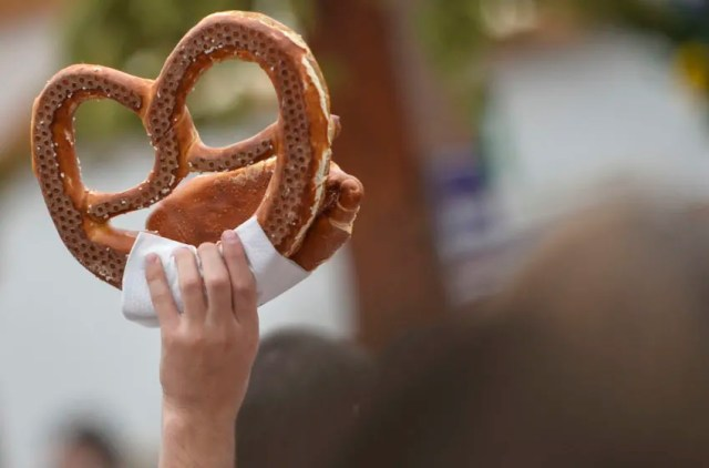 MUNICH, GERMANY - SEPTEMBER 19: A vendor holds a pretzel at the Hofbraeu tent on the opening day of the 2015 Oktoberfest on September 19, 2015 in Munich, Germany. The 182nd Oktoberfest will be open to the public from September 19 through October 4 and will draw millions of visitors from across the globe in the world's largest beer fest. (Photo by Philipp Guelland/Getty Images)