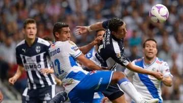 Rayados de Monterrey and Puebla players dispute a ball through the air.
