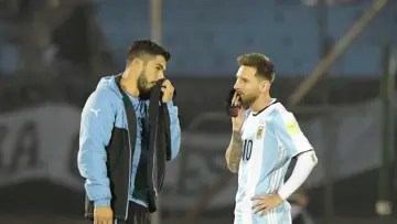 Uruguay v Argentina - FIFA 2018 World Cup Qualifiers - Messi and Suárez chat on the pitch.