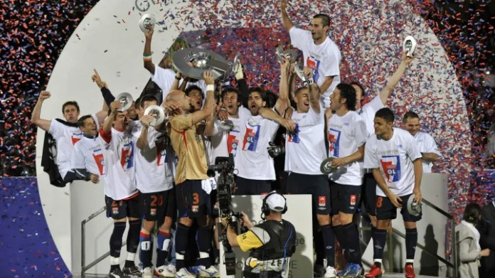 Lyon's players hold the trophy as they c