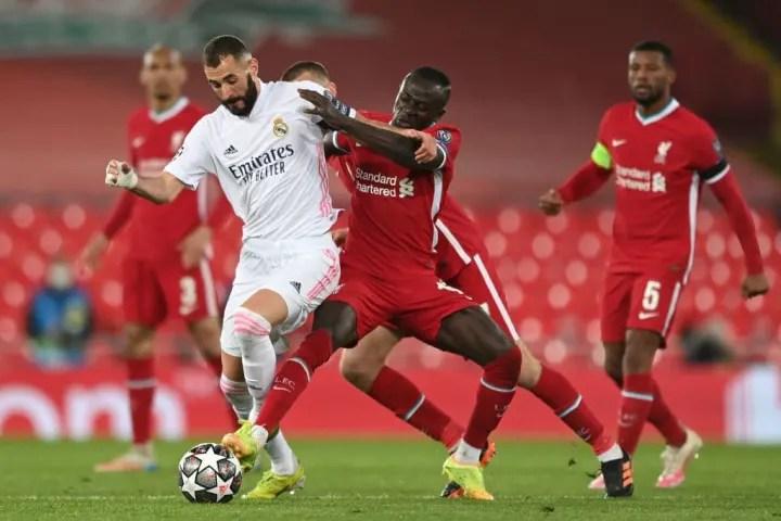 Real Madrid's Karim Benzema takes on Liverpool's Sadio Mane