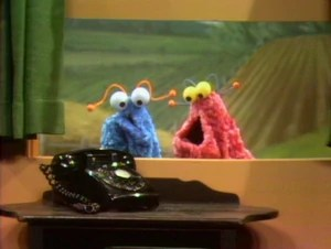 Two smarter Muppets than Elmo try to communicate with a telephone.