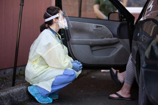 Oregon Health & Science University nurse practitioner Shelby Freed talks to a patient before testing them for COVID-19 at a drive-up station in Portland, Ore., Friday, March 20, 2020. Proper PPE includes a mask, face shield, gown, gloves and shoe covers.