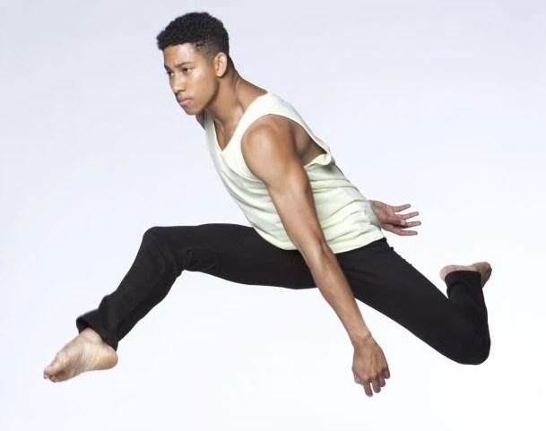 A young black male ballet dancer, captured mid-leap.