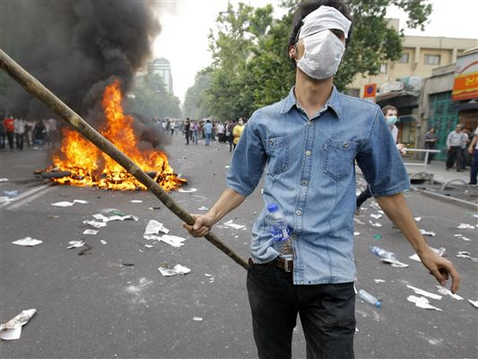 A Musavi supporter walks past a burning motorcycle during the opposition protests.